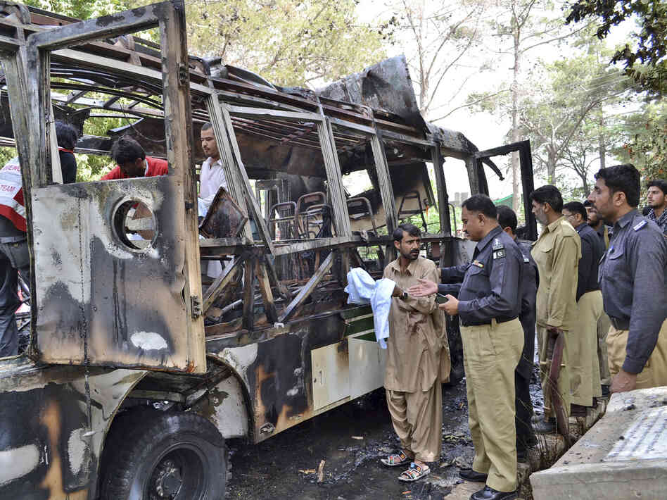 Pakistani police officers and volunteers gather at the wreckage of a bus destroyed in a bomb blast in Quetta, Pakistan, on Saturday.