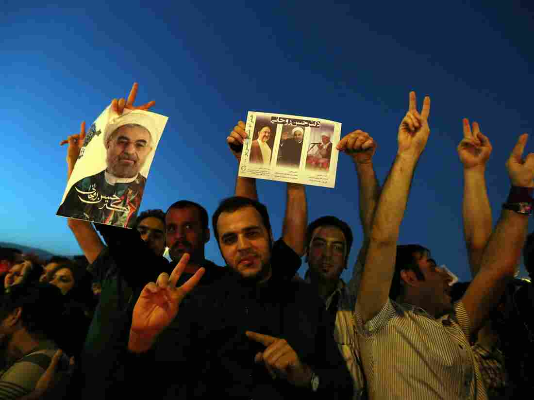 Iranians celebrate the victory of moderate presidential candidate Hasan Rowhani (portrait) at Vanak square in northern Tehran on Saturday.