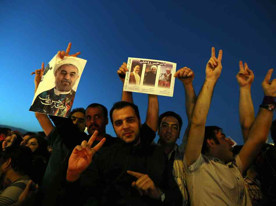 Iranians celebrate the victory of moderate presidential candidate Hasan Rowhani (portrait) at Vanak square in northern Tehran on Satur