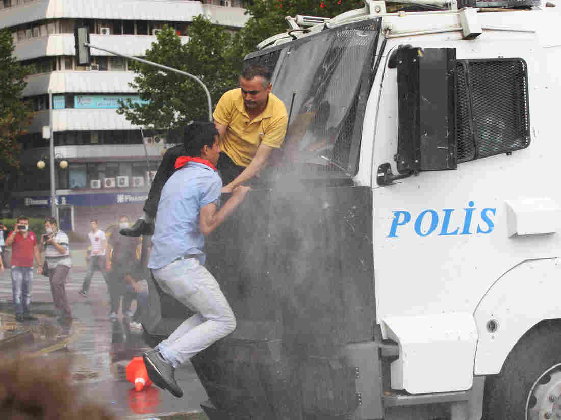 Protesters climb onto a police truck mounted with a water cannon during clashes with riot police at a demonstration in Ankara on Sunday.