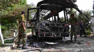 Pakistani security personnel inspect a burned-out bus on Sunday, a day after it was destroyed by a bomb attack in Quetta. The bus was carrying students from the region's only university for women. Fourteen women died.