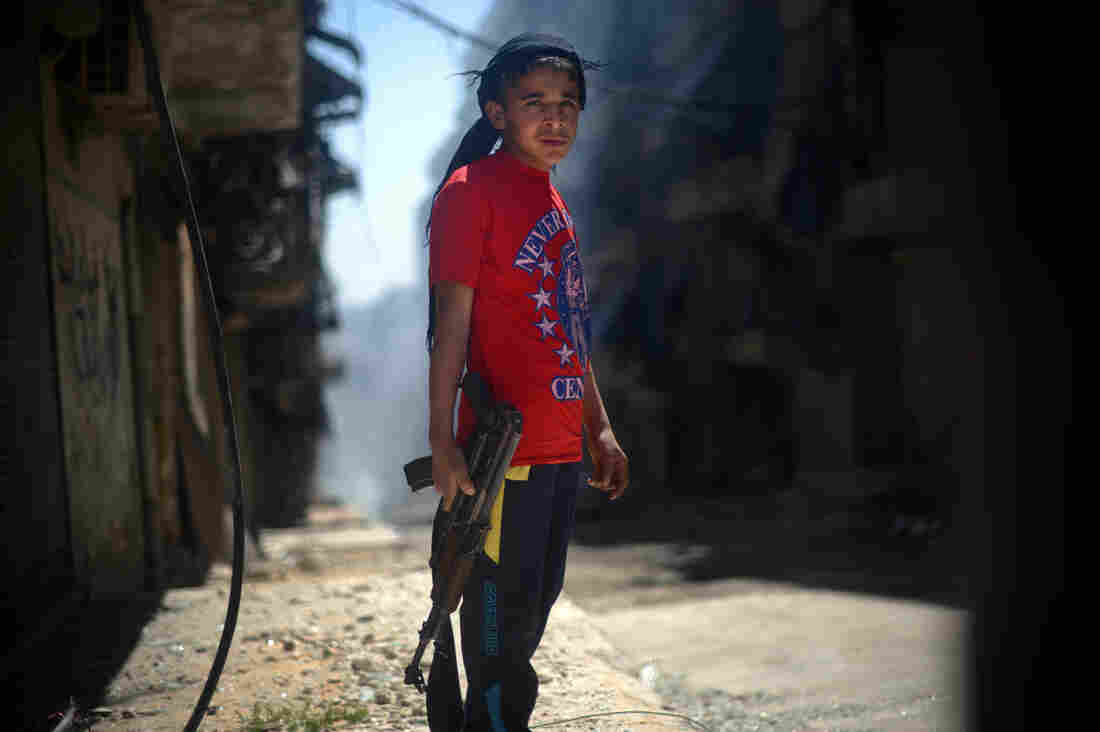 A Syrian boy holds an AK-47 assault rifle in the majority-Kurdish Sheikh Maqsud district of the northern Syrian city of Aleppo in April.