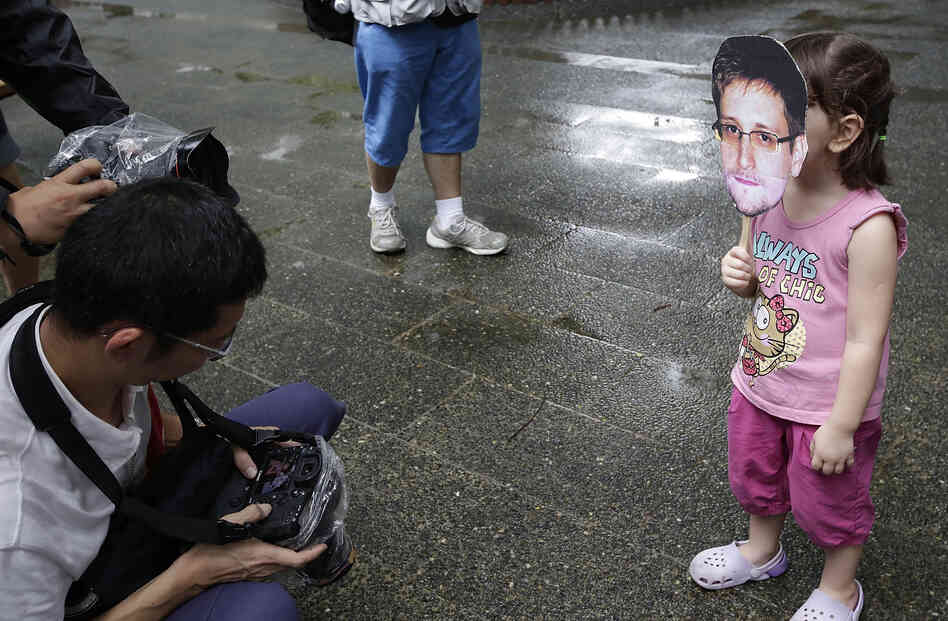 A young girl holds up a cutout image of Edward Snowden's face at the start of a rally in support of the NSA leaker over
