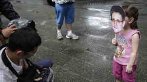 A young girl holds up a cutout image of Edward Snowden's face at the start of a rally in support of the NSA leaker over the weekend in Hong Kong.