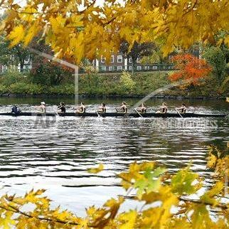 A crew team rows past Harvard University down the Charles River which separates Cambridge and Boston Saturday, Oct. 24, 2009 in Cambridge, Mass.