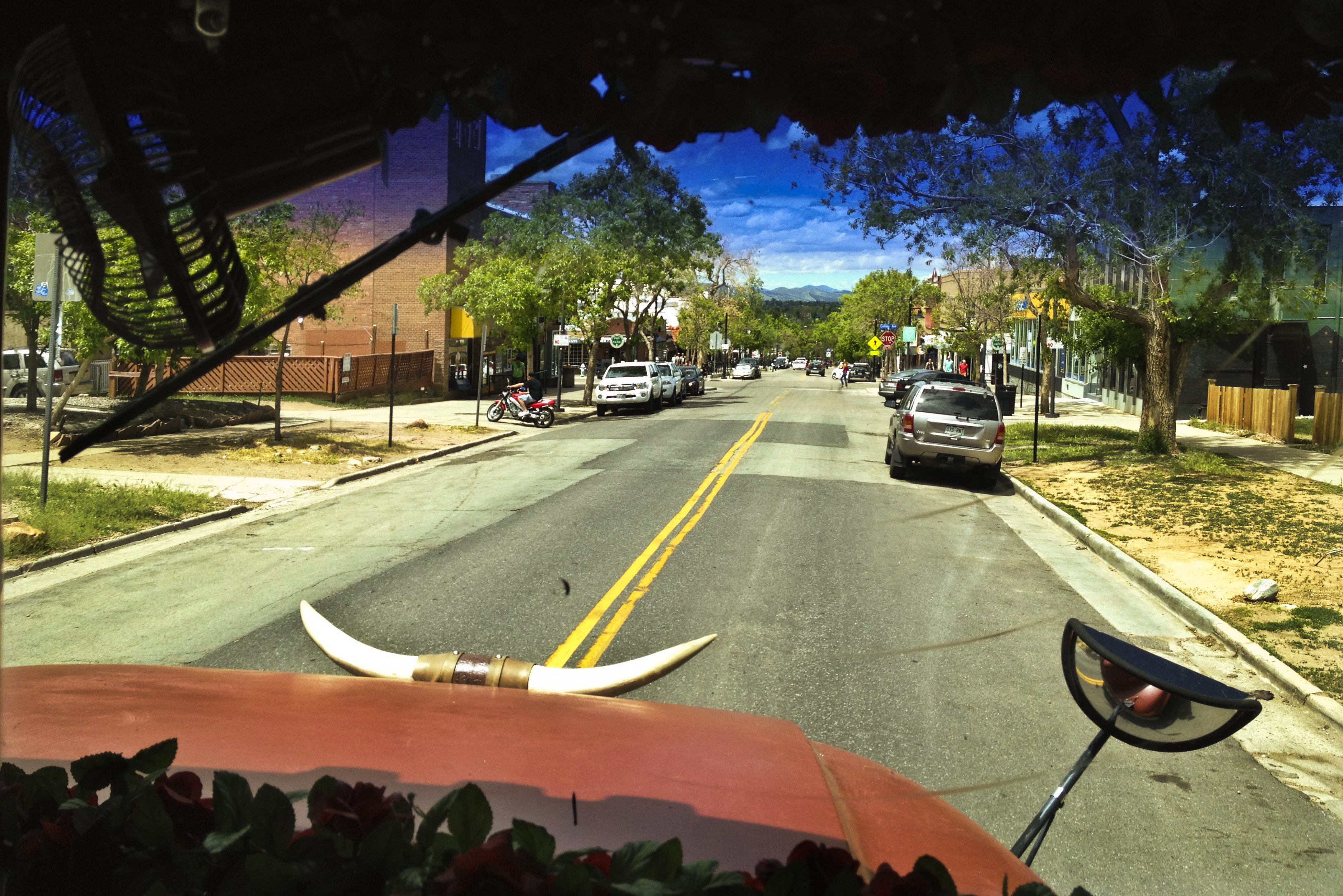 The Banjo Billy bus cruises along 13th Street on Boulder's University Hill. The brick building on the left is home to the historic Flatirons Theatre, which figures into one of Billy's more grisly tales.
