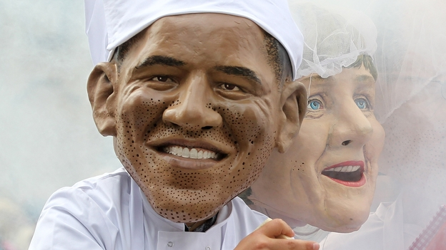 Oxfam charity volunteers wear masks depicting G-8 leaders President Obama and German Chancellor Merkel around a large caldron to draw attention to the issue of world hunger in Northern Ireland on Sunday. G-8 leaders are gathering there for an annual summit. (AFP/Getty Images)