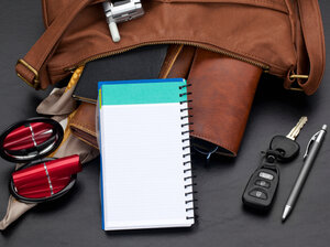 Personal organizer with blank lined page propped against various items spilling out of a brown leather purse. Studio isolated on a black textured background.