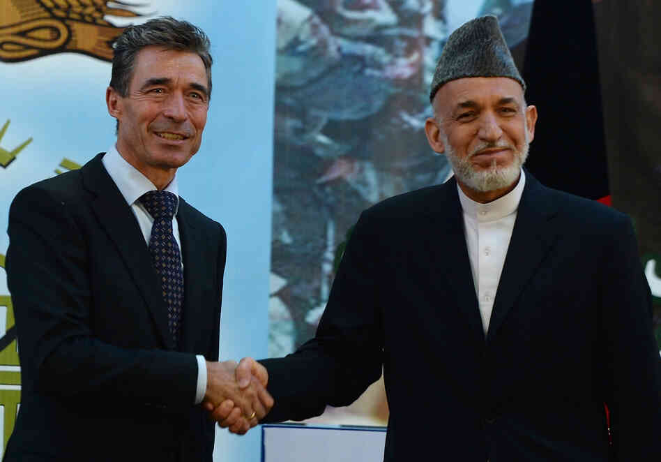 Afghan President Hamid Karzai shakes hands with NATO Secretary-General Anders Fogh Rasmussen after a security handover ceremony at a military academy outside Kabul on Tuesday.