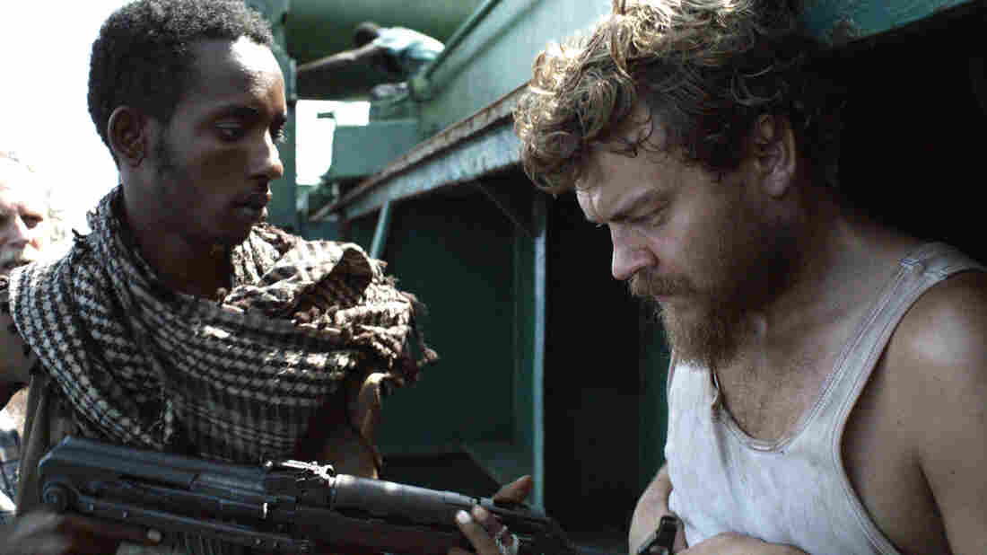 Pilou Asbaek (right) plays ship's cook Mikkel, a new dad who desperately wishes to return to his family, but is instead forced to prepare menus at gunpoint as the cargo vessel's owners negotiate for its release.