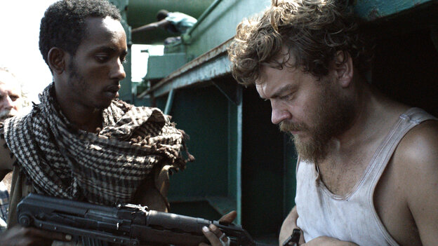 Pilou Asbaek (right) plays ship's cook Mikkel, a new dad who desperately wishes to return to his family, but is instead forced to prepare menus at gunpoint as the cargo vessel's owners negotiate for