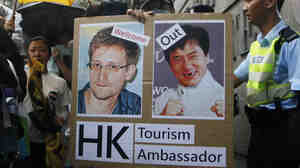 A supporter holds a sign with pictures of Edward Snowden, the former National Security Agency contractor who leaked details about the agency's surveillance programs, and Hong Kong movie star Jackie