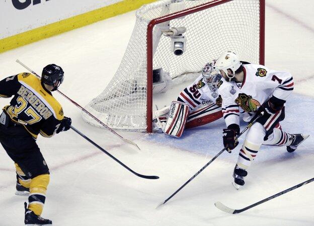Boston Bruins center Patrice Bergeron (37) sends the puck past Chicago Blackhawks goalie Corey Crawford on Monday night.