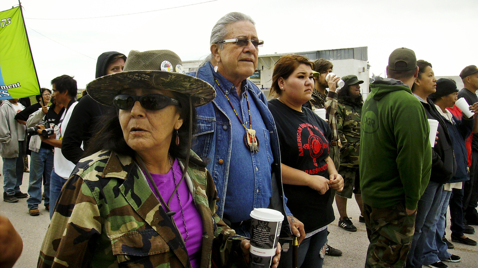 Oglala Lakota activist Debra White Plume (left), tribal president Bryan Brewer (center) and other protesters create a blockade to prevent trucks from delivering beer to a liquor store in Whiteclay, Neb. The town, which borders the Pine Ridge Reservation, has been the site of recurring protests over alcohol. (Charles Michael Ray/SDPB)