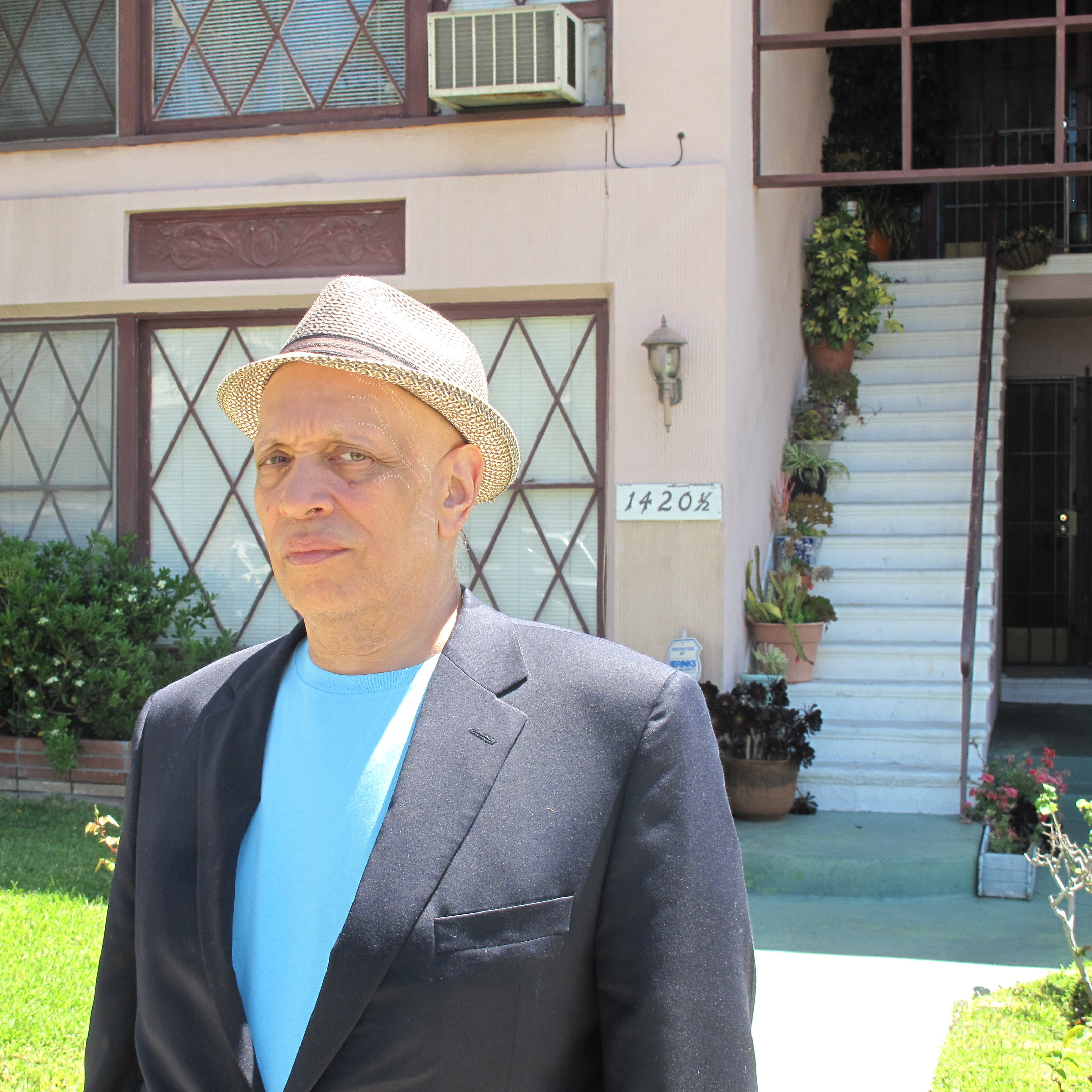 Walter Mosley stands in front of the house his parents owned, near the Pico-Fairfax neighborhood in Los Angeles. Many of the landmarks he knew as a child find their way into his books.