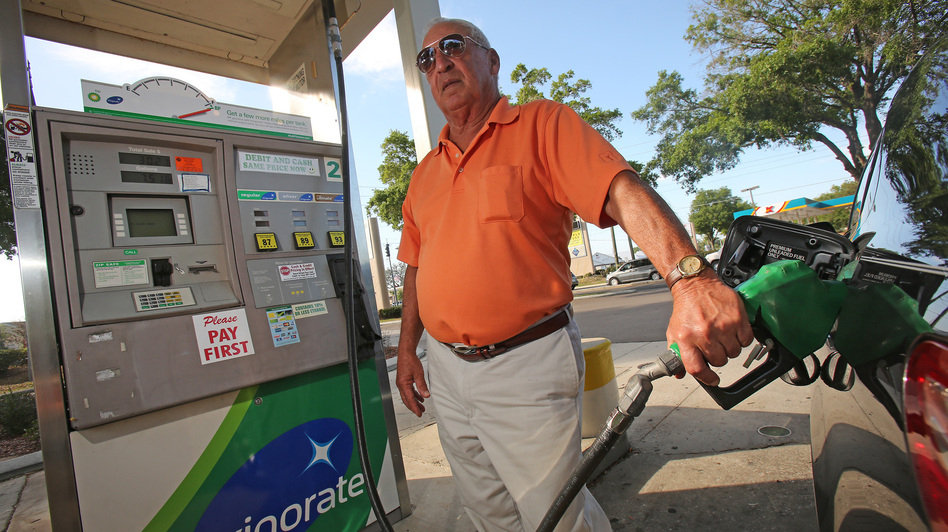 Jim White of Pennsylvania pumps gas at a BP station in Ocala, Fla., in April. The price of gasoline remains stubbornly high, which may put a crimp on summer travel plans. (Ocala Star-Banner / Landov)