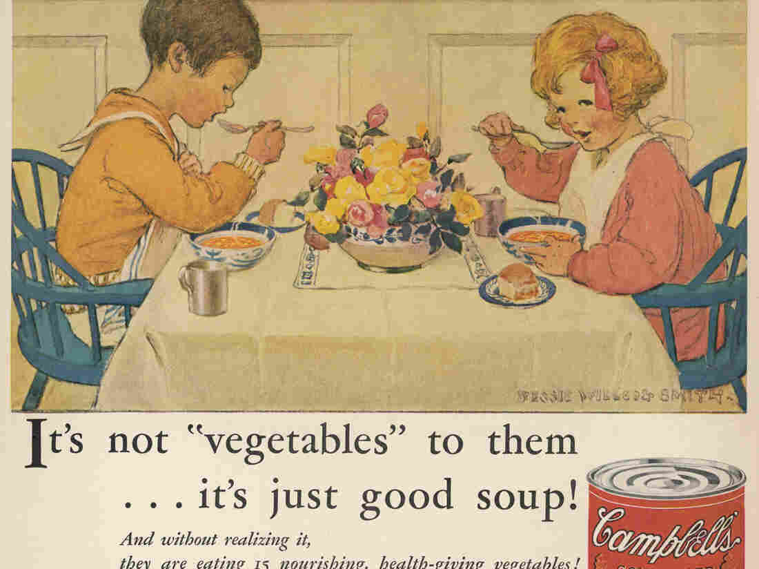 Two children with napkins around their necks  enthusiastically tuck in to a steaming bowl of Campbell's vegetable soup in this vintage ad.