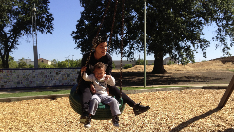 Micaela Torres and 2-year-old Jakai Johnson swing underneath a surveillance camera at Miwok Park in Elk Grove, Calif. The city's police department collects more than 100 video feeds from across the city. (NPR)