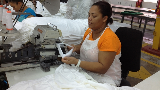 "Aracelis Upia Montero works at the Alta Gracia garment factory in the Dominican Republic. She says she was desperately poor before she began working at the factory, which pays much higher than usual wages. ""I'm now eligible for loans and credits from the bank because I earn a good salary,"" she says. (NPR)"