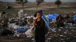 Afghan refugee children collect items of use from a pile of garbage on the outskirts of Islamabad, Pakistan.