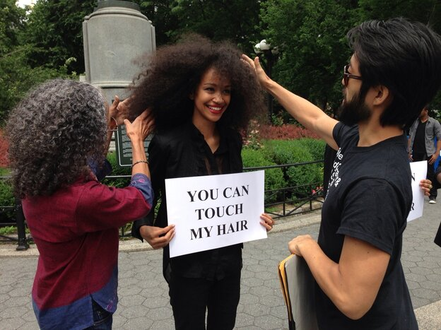 Model Malliha Ahmad holds a sign inviting passersby to touch her hair.