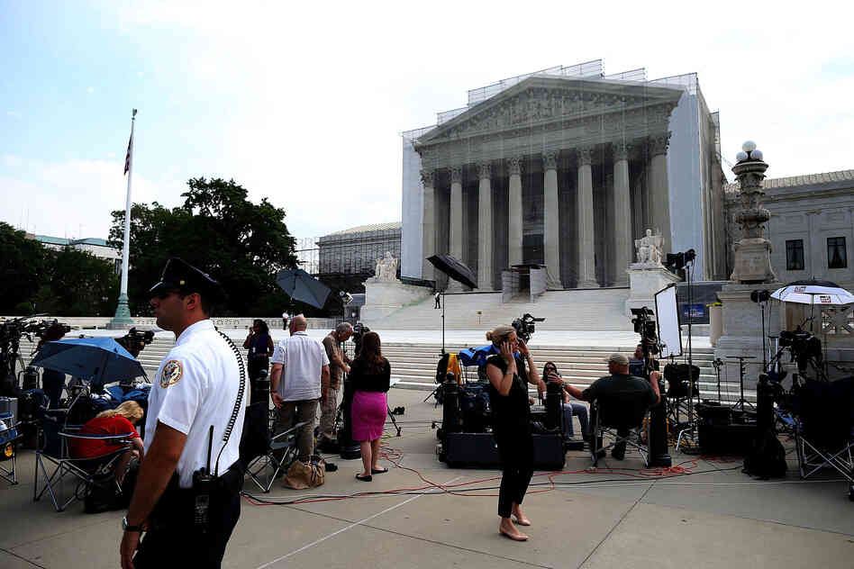 Members of the media wait for court rulings in front of the U.S. Supreme Court building on Monday.