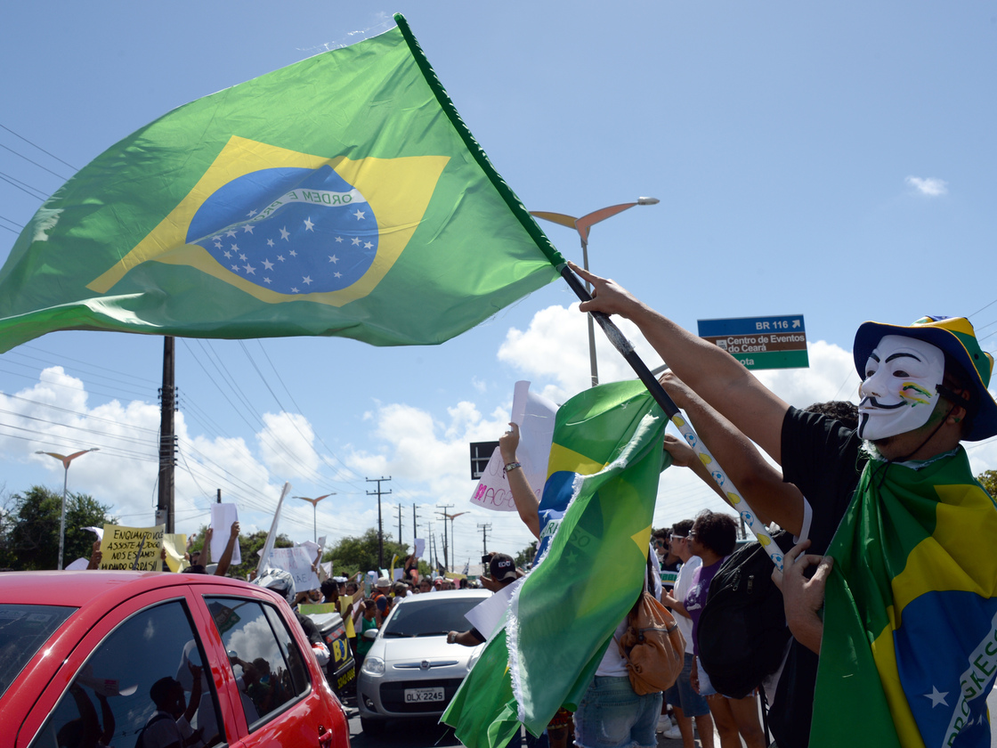 lxl v for vendetta notes a protester waves a ian flag over cars driving to the football stadium in fortaleza
