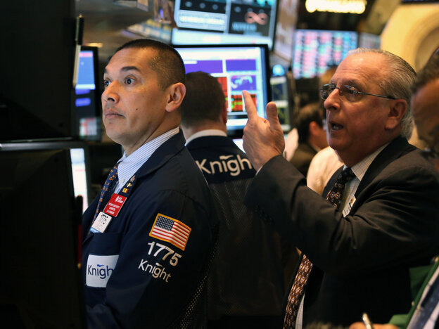 Traders work the floor of the New York Stock Exchange after the opening bell on Thurs