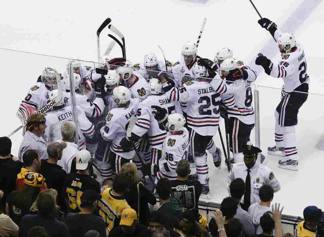 The Chicago Blackhawks mob Brent Seabrook after his game-winning goal against the Boston Bruins in overtime of the NHL hockey Stanley Cup Finals on Wednesday night in Boston.