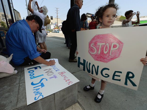 Gracie Shannon-Sanborn, 5, holds a sign as she joins her father Allen Sanborn (L) and members of Progressive Democrats of America at a rally in front of Rep. Henry Waxman's offic