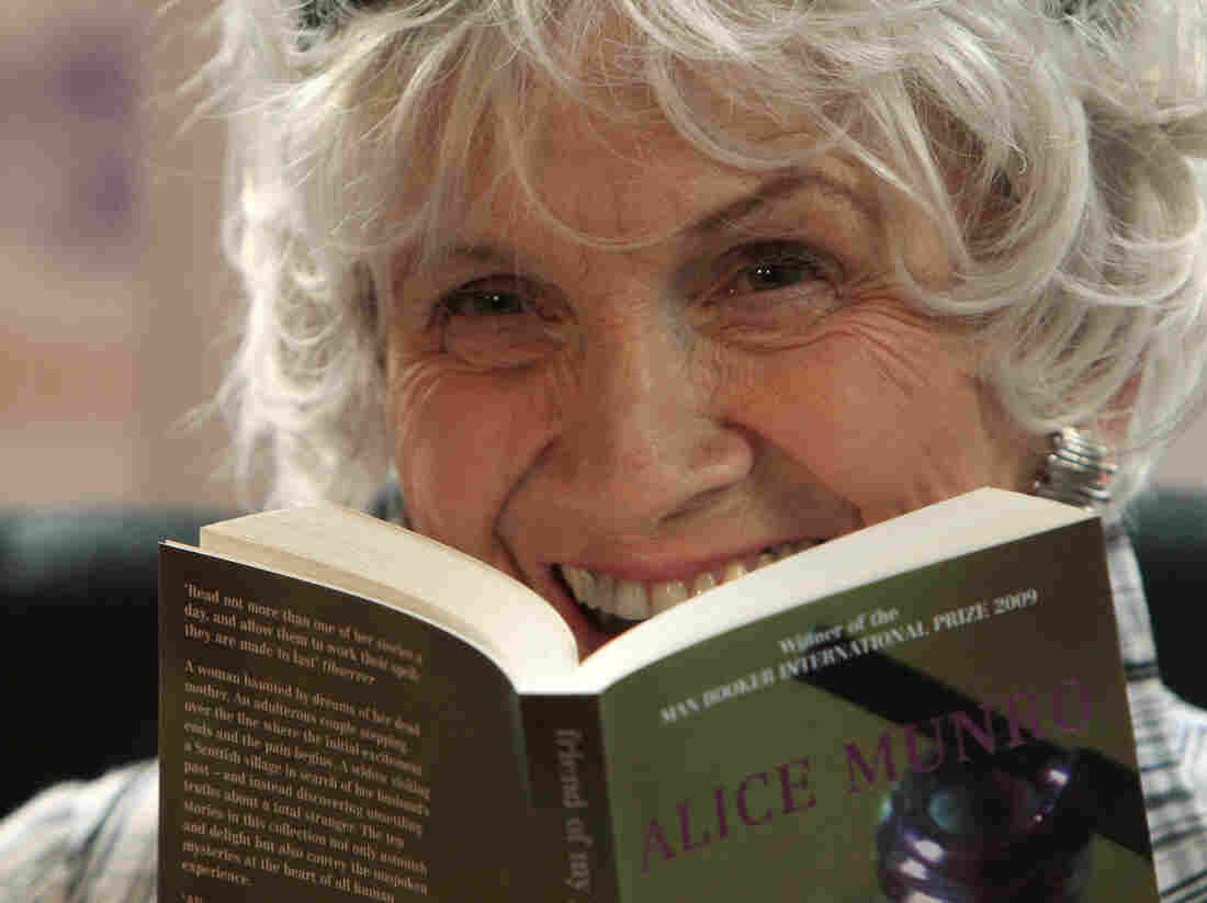 Alice Munro holds up one of her books as she receives the Man Booker International award at Trinity College Dublin on June 25, 2009.