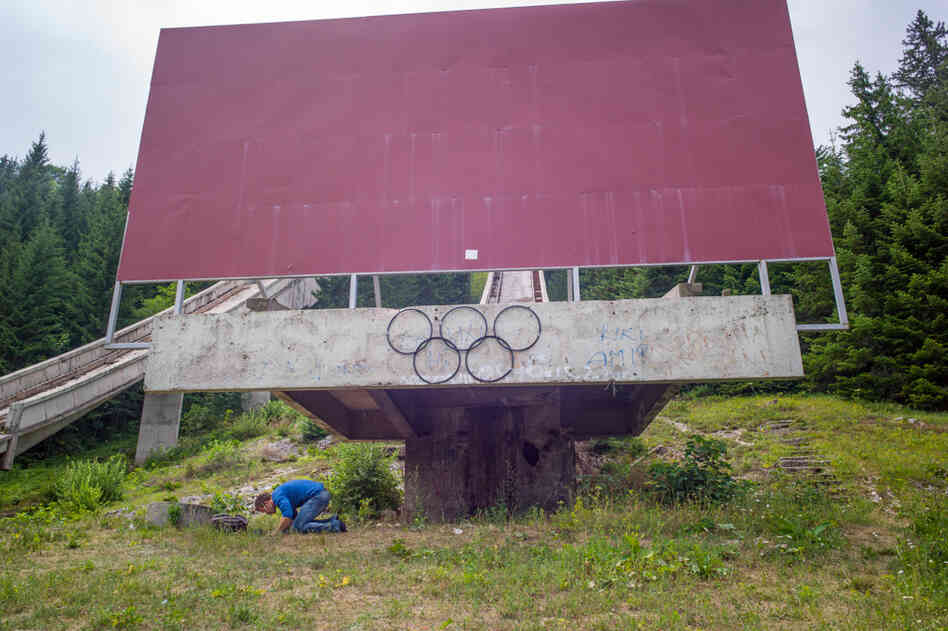 A man prays during Ramadan beneath handmade Olympic rings on one of the former ski jumps in Sarajevo, where the 1984 Winter Games were held.