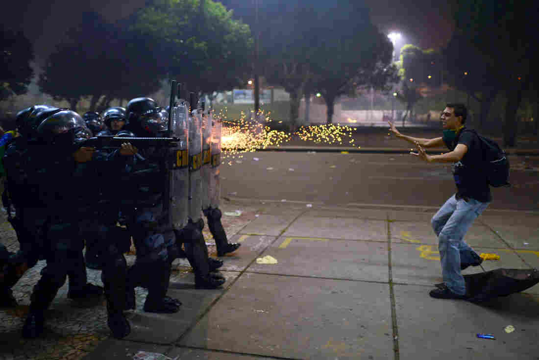 A demonstrator is shot by a rubber bullet as anti-riot police officers charge during a protest Thursday against corruption and price hikes in Rio de Janeiro.