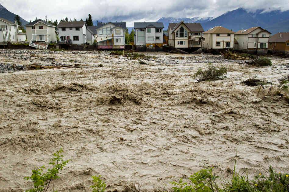 Houses damaged along the edge of Cougar Creek in Canmore, Canada. Widespread flooding caused by torrential rains washed out bridges and roads prompting the evacuation of thousands on Thursda