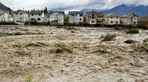 Houses damaged along the edge of Cougar Creek in Canmore, Canada. Widespread flooding caused by torrential rains washed out bridges and roads prompting the evacuation of thousands on Thursday.