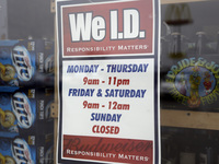 A sign on a window at an Elite Beverages liquor store in Indianapolis lists the store's hours.