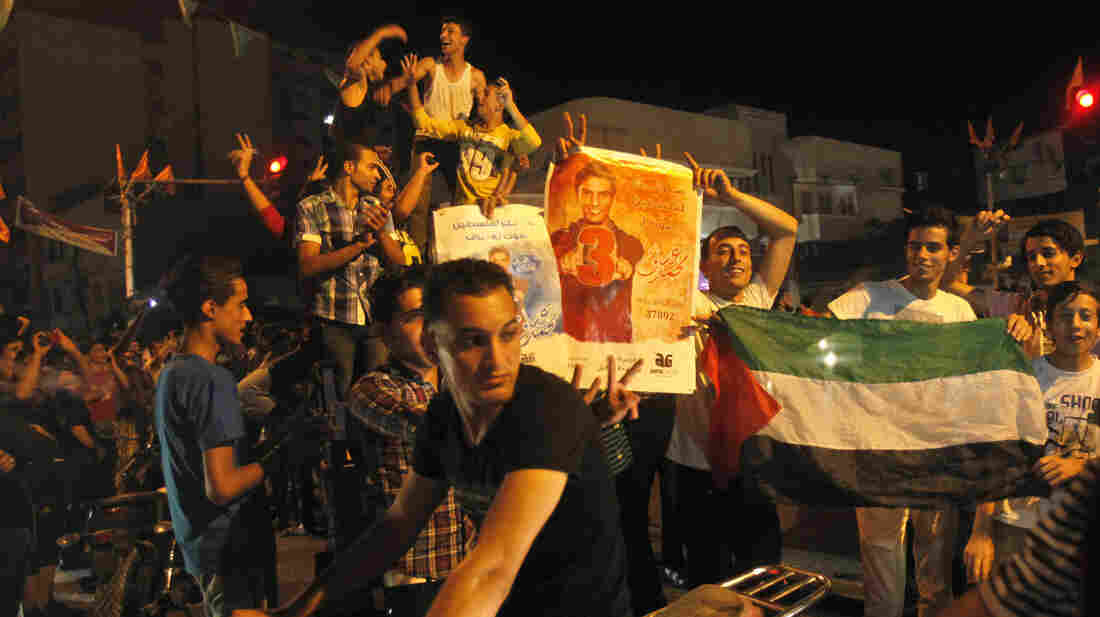 Palestinians dance with pictures of singer Mohammed Assaf as they celebrate his Arab Idol victory along the streets of Gaza City Saturday.