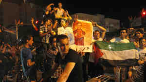 Palestinians dance with pictures of singer Mohammed Assaf as they celebrate his Arab Idol victory along the streets of