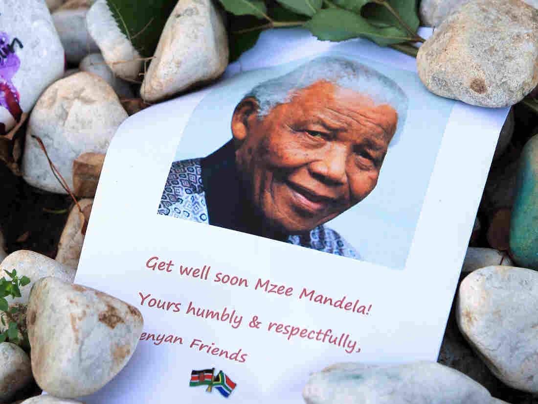 A print of Nelson Mandela and get well messages lay outside the home of the former President Mandela in Johannesburg, South Africa earlier this month.