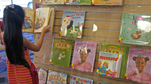 At a San Jose, Calif. library, a young reader browses a shelf of books featuring a variety of main characters: ducks, hens, white kids, black kids. Libraries help drive demand for children's books with nonwhite characters, but book publishers say there aren't enough libraries to make those books best-sellers. (Flickr)