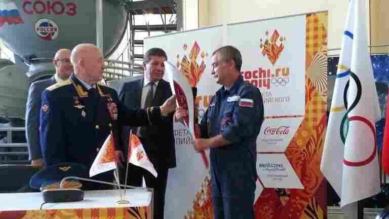 Former cosmonaut Alexey Leonov, left, the first man to perform a spacewalk, passed an Olympic torch to Mikhail Tyurin, who will lead the mission to the International Space Station in November.