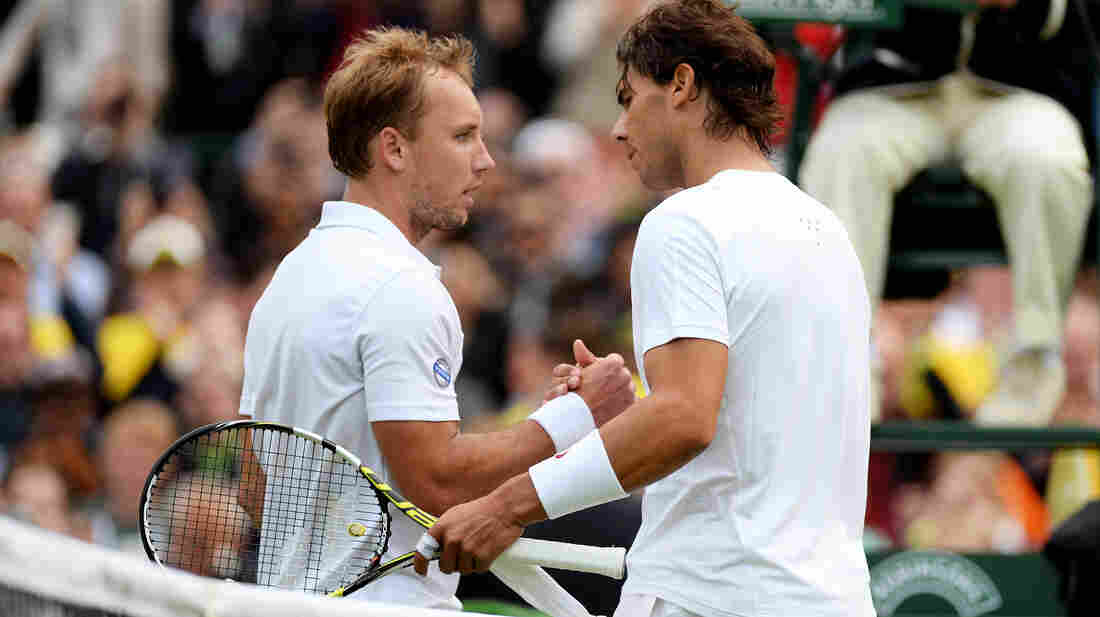 Steve Darcis of Belgium, left, shakes hands with Rafael Nadal of Spain Monday, after winning their first-round match at the Wimbledon Lawn Tennis Championships at the All England Lawn Tennis and Croquet Club.