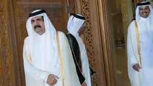 Qatari Emir Sheikh Hamad bin Khalifa al-Thani, left, and his son Sheikh Tamim bin Hamad bin Khalifa al-Thani, right, await France's President Francois Hollande prior to a welcoming ceremony earlier this month.