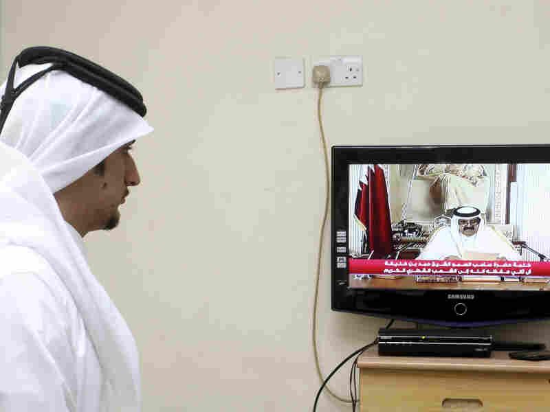 A man watches a televised address by Qatar's Emir Sheik Hamad bin Khalifa al-Thani, in Doha, Qatar, on Tuesday. Qatar's ruler transferred power to his 33-year-old son, making him the youngest leader in the region.