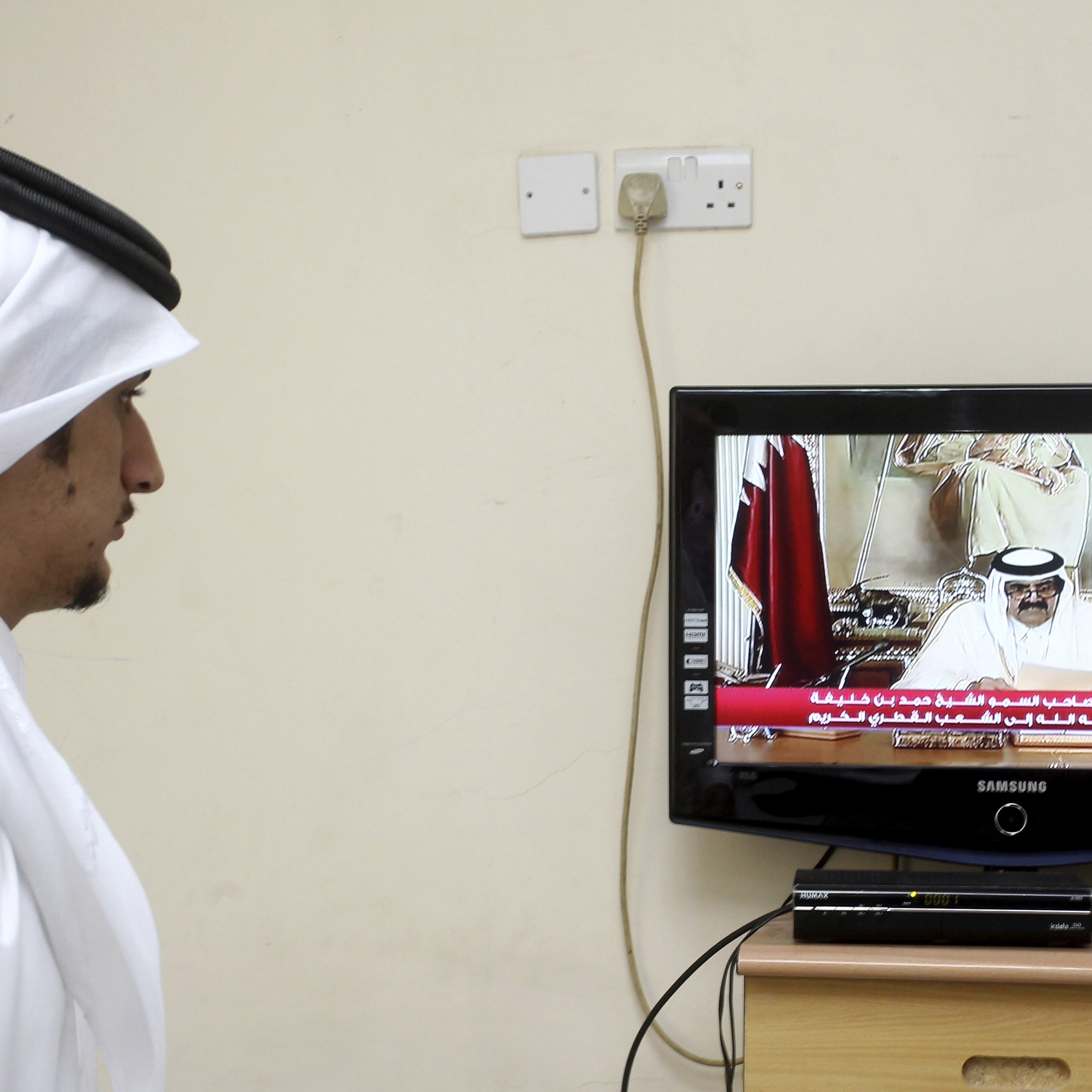 A man watches a televised address by Qatar's Emir Sheik Hamad bin Khalifa al-Thani, in Doha, Qatar, on Tuesday. Qatar's ruler transferred power to his 33-year-old son, making him the youngest leader in the region.
