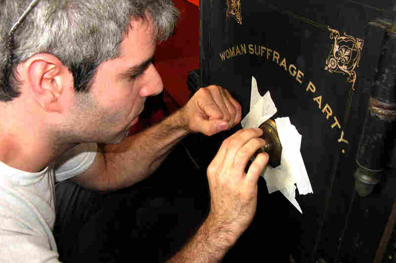 Safe cracker Elaad Israeli works the dial on an old safe found by the National Council of Women of the United States.