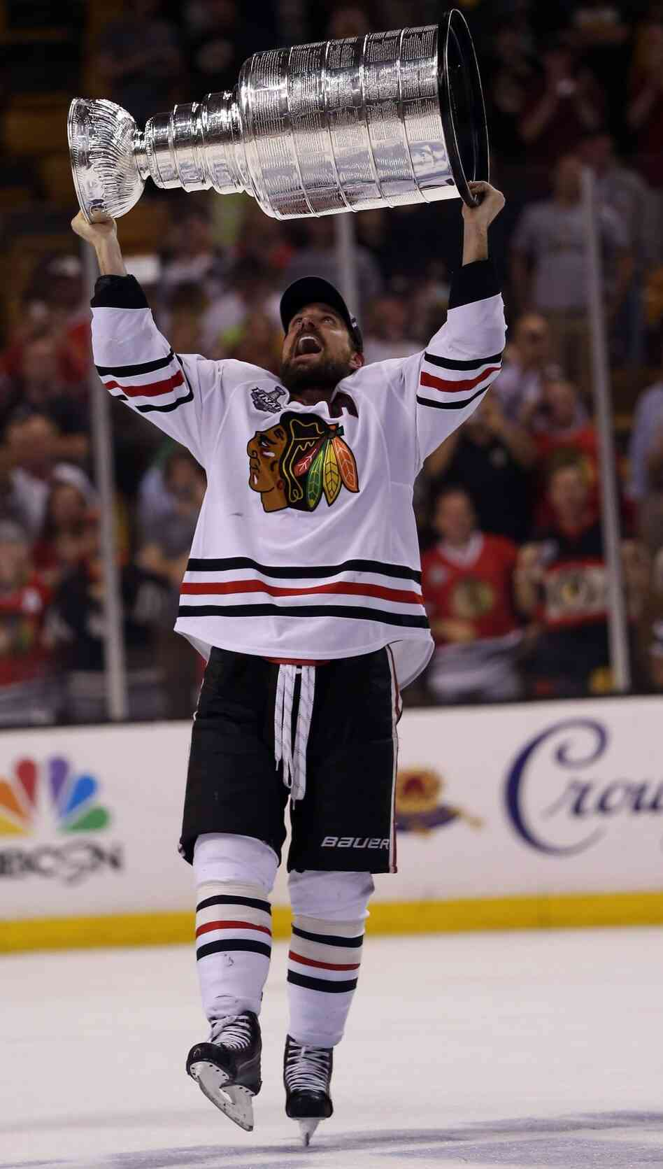 Blackhawks center Patrick Sharp lifts the Stanley Cup after Chicago's series-clinching win Monday night in Boston.
