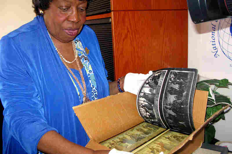 Mary Singletary, president of the National Council of Women, holds a box full of the mural replicas that were inside the safe.