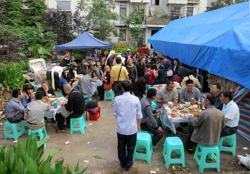 Dozens of friends and family of the deceased, Zhang Tujin, gather to feast on a big pre-funeral meal and celebrate his life. The meal takes place outside, in the shadow of a modern apartment block,