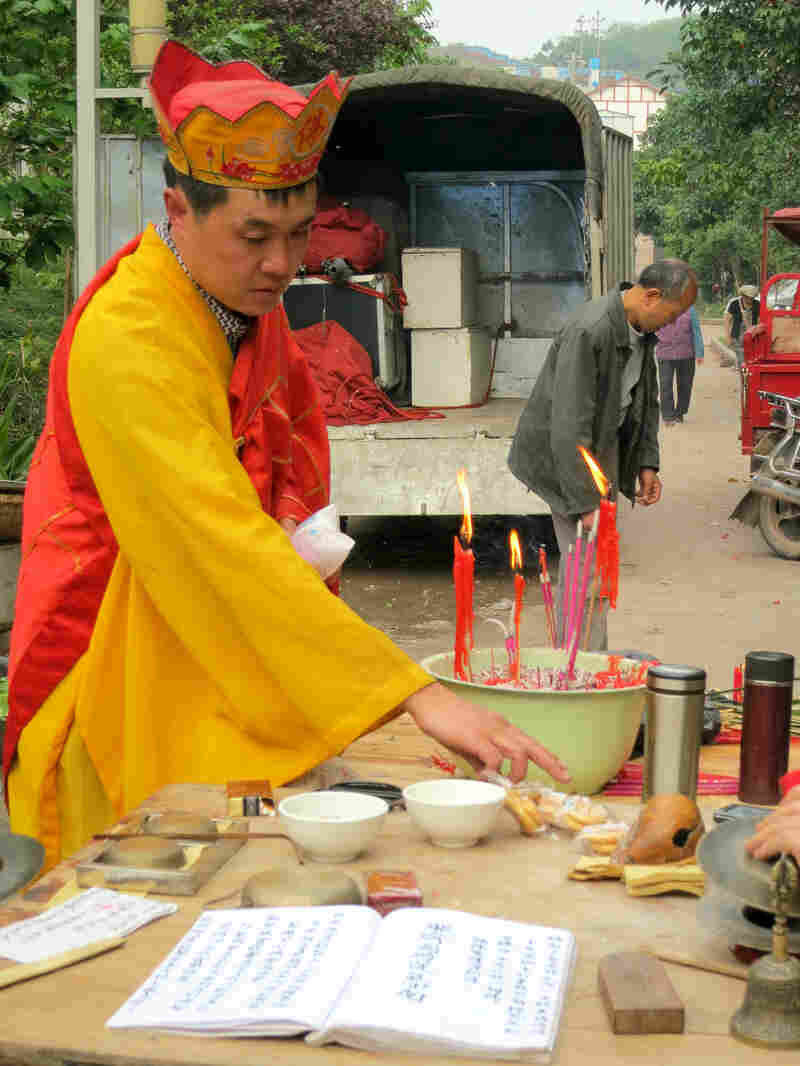 "An actor chants and burns paper offerings to the dead. His costume is similar to those worn by the monk in the Chinese epic ""Journey to the West."""